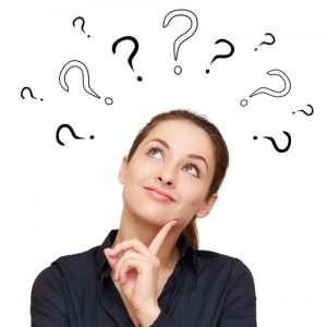 Woman looking up at question marks above her head
